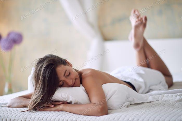 Mujer seductora en la cama por la mañana.