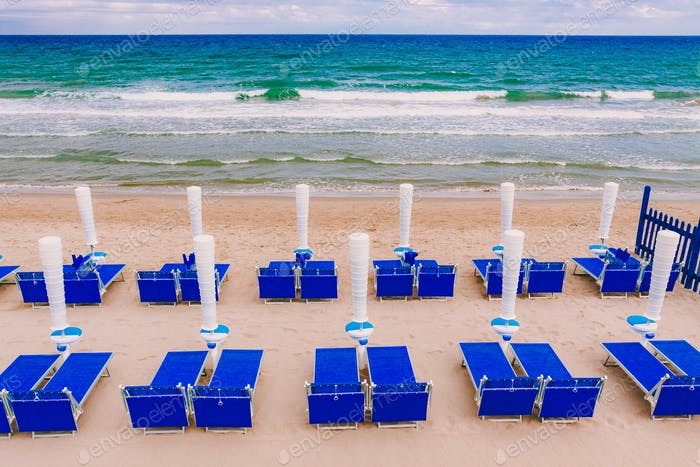 Umbrellas and sun beds on the beach at the Sea or ocean in a summer day