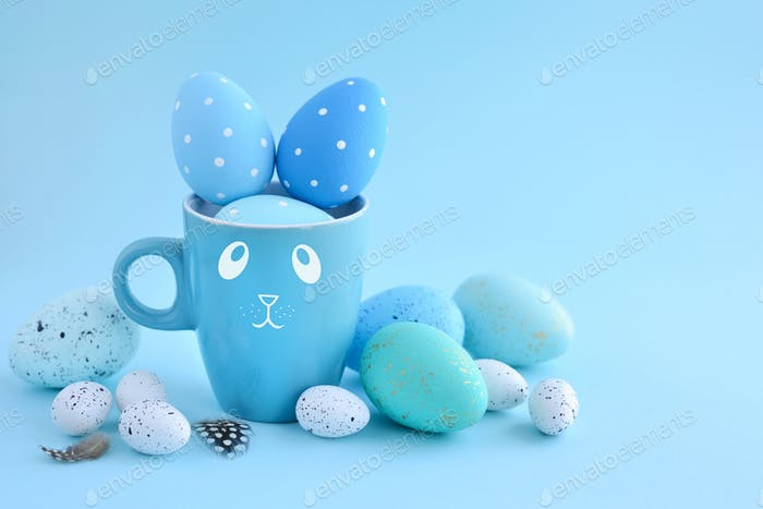 Easter eggs and a cup in the form of a rabbit on a blue backgrou