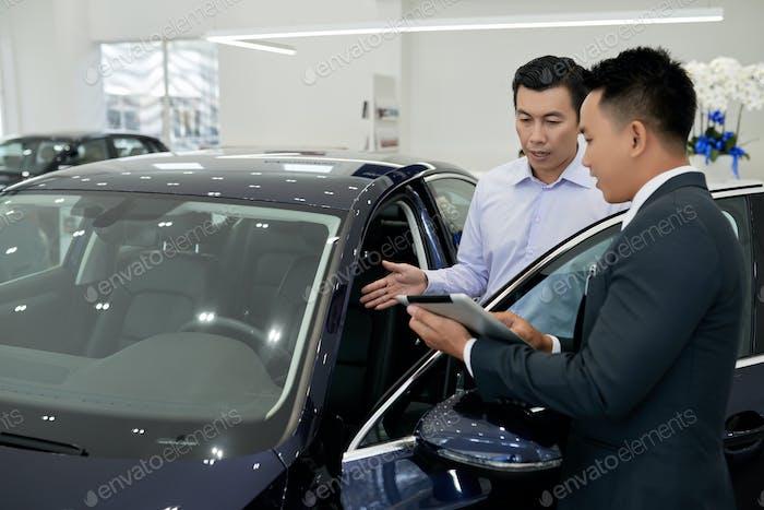 Salesman showing car
