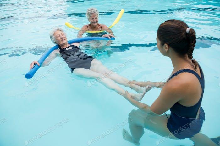 Female coach helping senior women in swimming pool