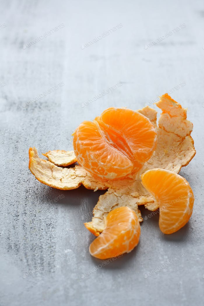 Open fresh mandarin on gray background