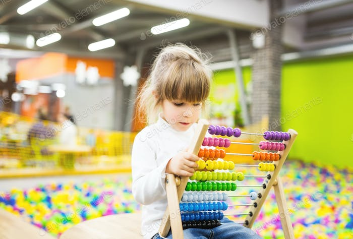 Girl playing with a wood abacus toy