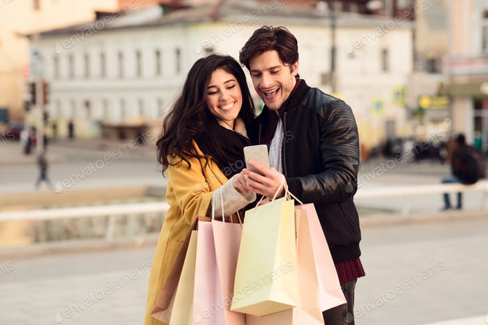 Millennial couple with cellphone calling taxi, walking outdoors