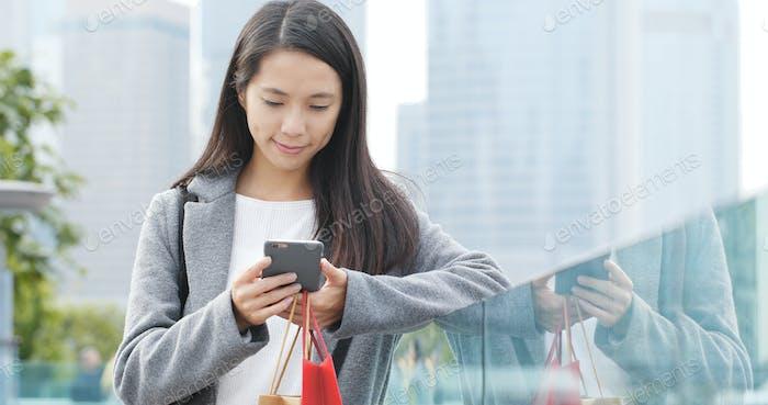 Frau Blick auf Handy und halten Shopping im Freien