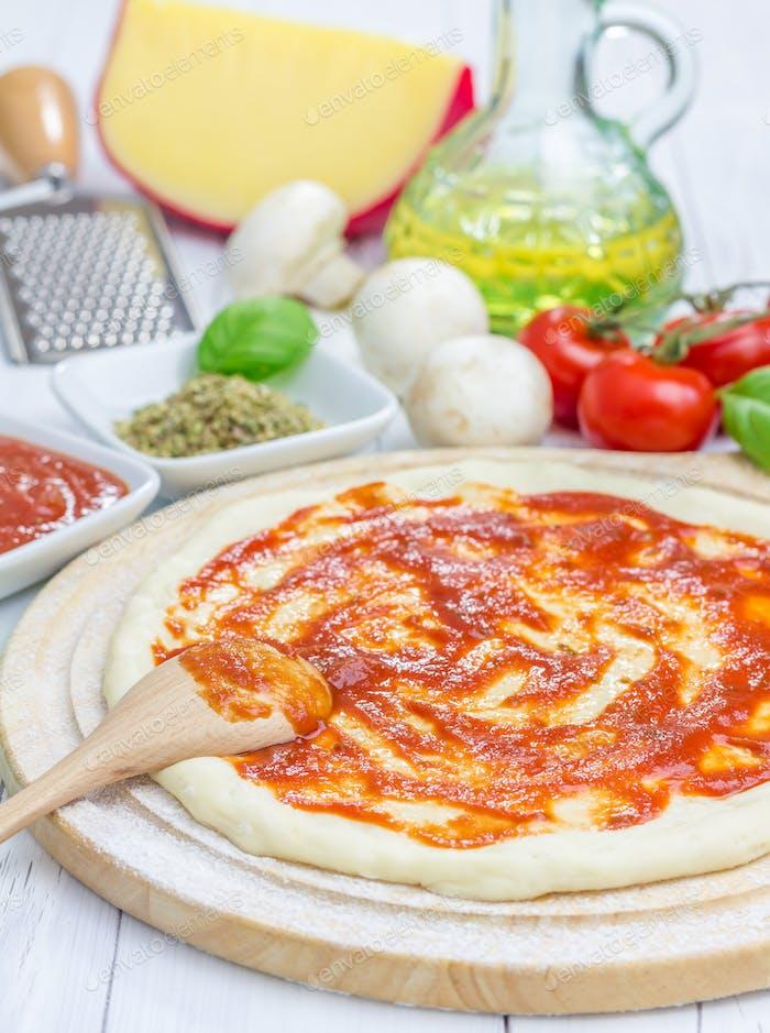 Pizzateig mit Tomatensauce auf einem Holzbrett