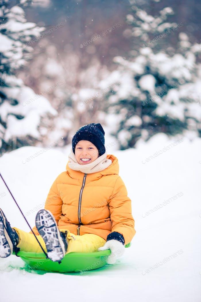 Adorable little happy girl sledding in winter snowy day