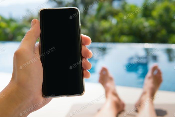 Smartphone in der Hand Nahaufnahme auf Pool Hintergrund