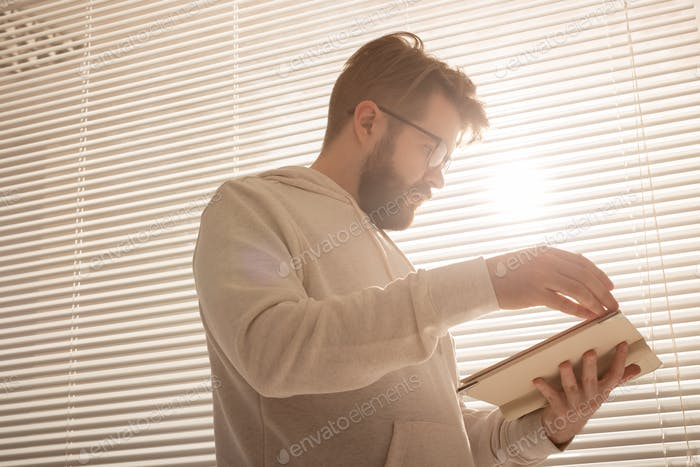 Bottom view of pensive stylish hipster man leafing through his daily planner