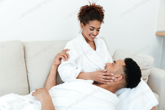 Happy african loving couple sitting indoors