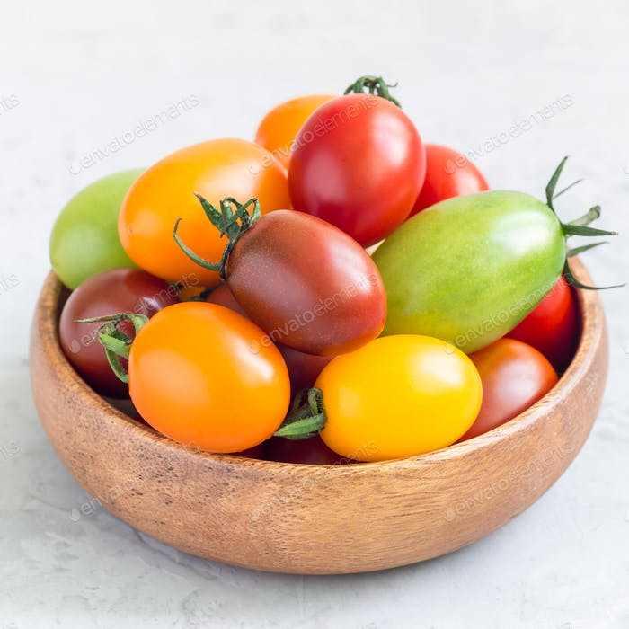 Small colorful cherry tomatoes in wooden bowl on a table, square format