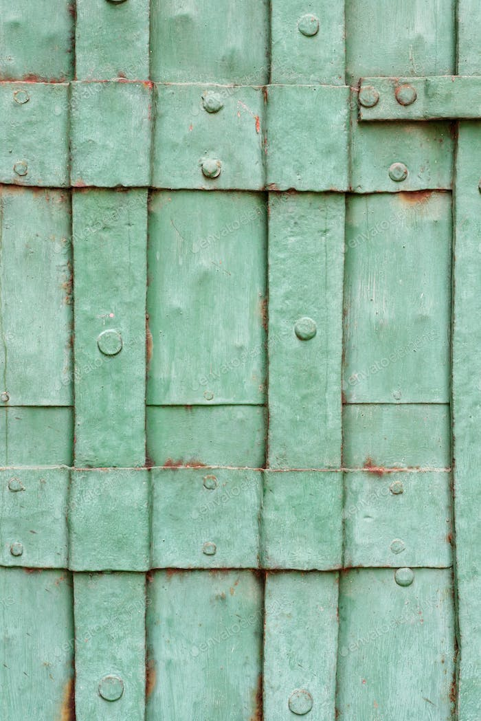 Old painted riveted metal door detail