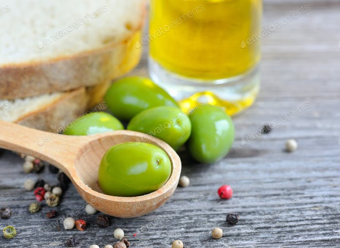 Green olives in a wooden spoon with oil and color peppers on a w