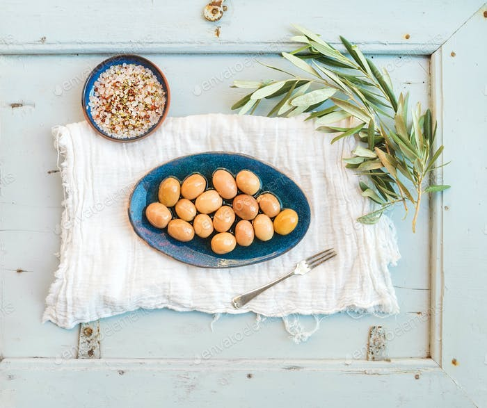 Grüne große Oliven in rustikaler Keramikplatte mit Ast und Gewürzen