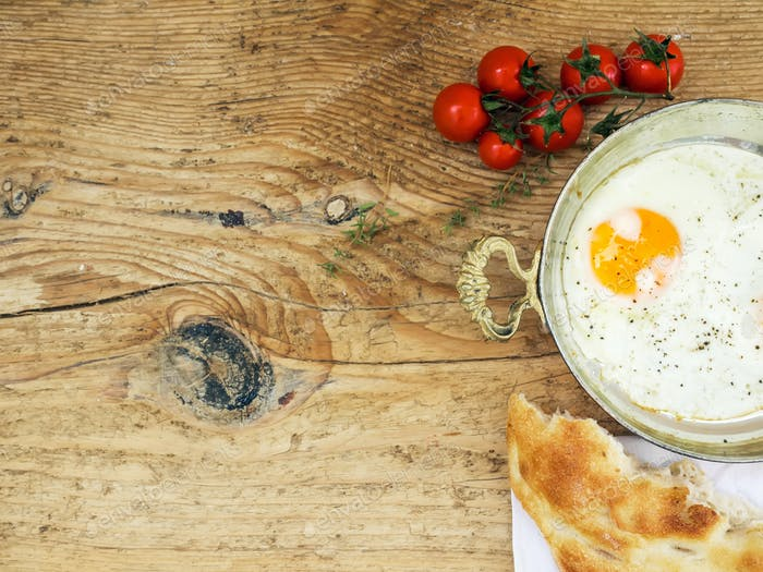 Breakfast set: fried egg, bread and cherry-tomatoes on a wooden