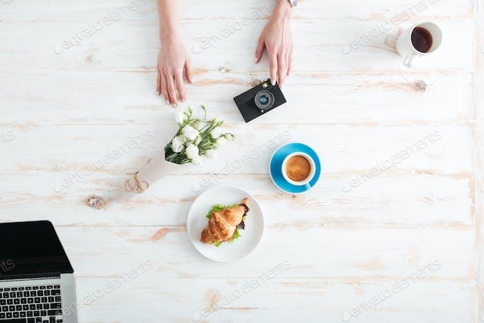 Weibliche Hände halten Kamera auf dem Holztisch