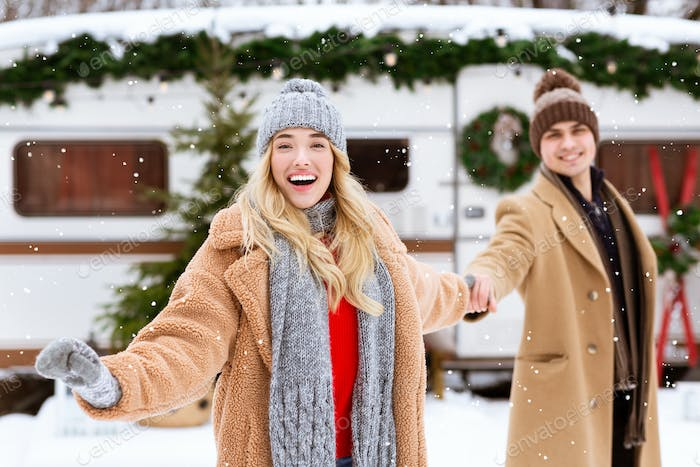 Cheerful Girl Leading Her Boyfriend To Watch Snowfall Outdoors On Winter Day
