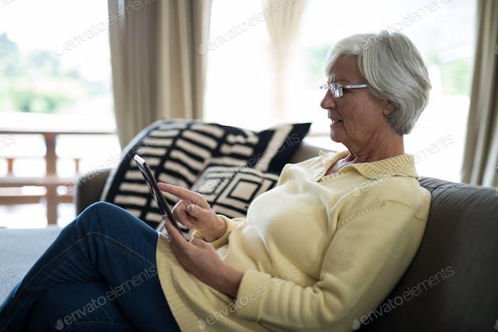Senior woman using digital tablet on sofa