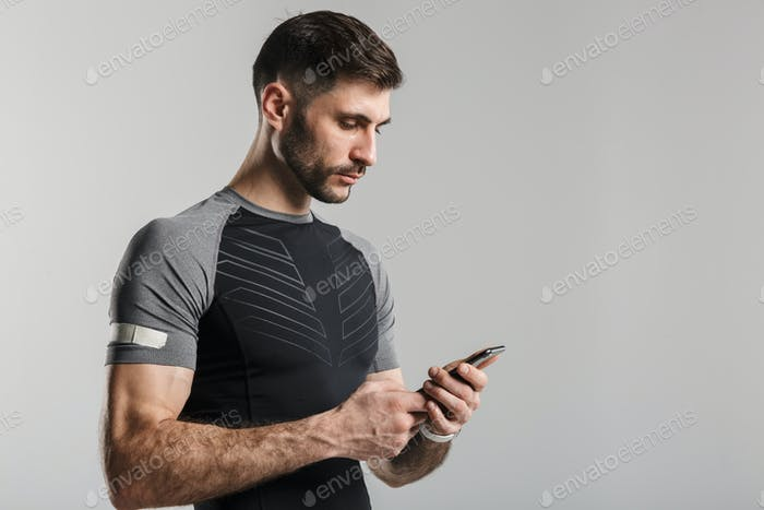 Image of young unshaven man posing and using cellphone