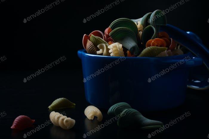 Colored spelt pasta in blue ceramic pot