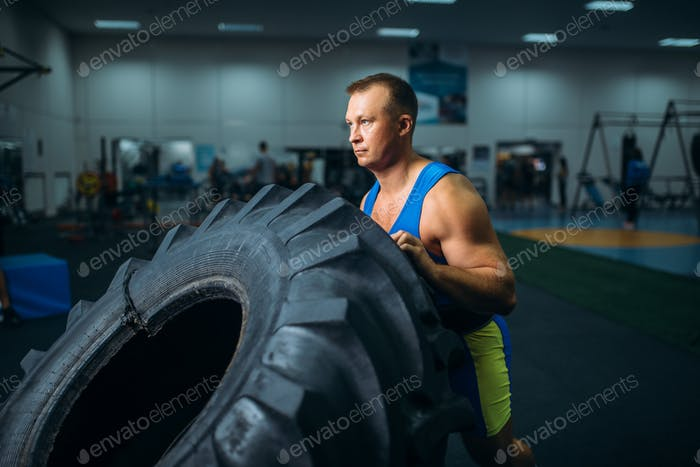 Athlete doing exercise with truck tyre, crossfit