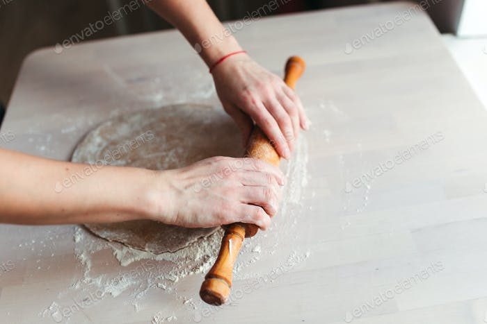 A woman pastry chef or baker preparing a cake.