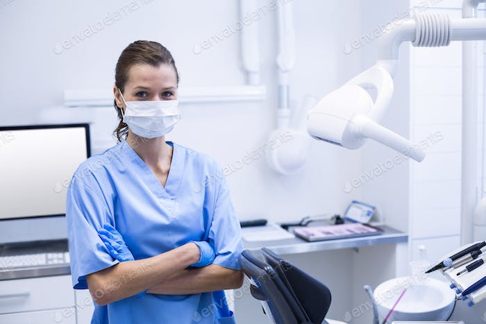 Smiling dental assistant standing with arms crossed