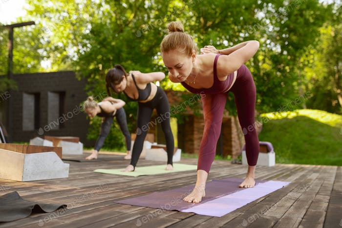 Women with perfect body on group yoga training