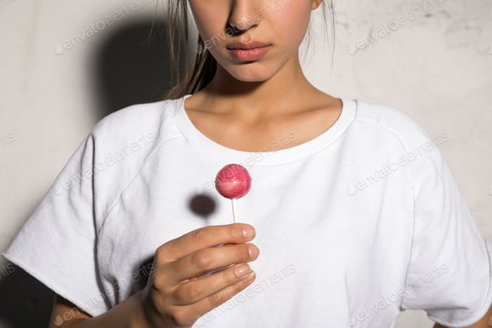 Cropped picture of young hipster woman holding candy.