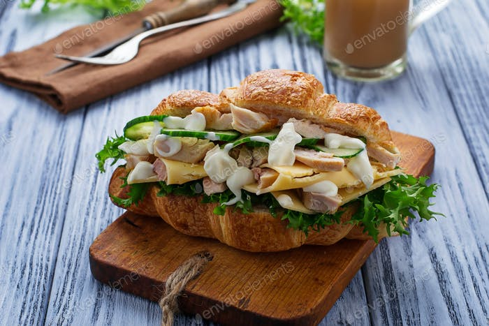 Croissant sandwich with chicken, cheese, cucumber