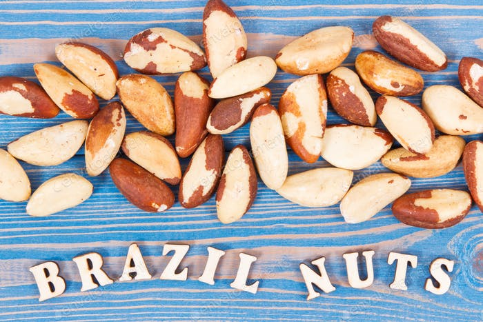 Inscription brazil nuts and heap of fruits as source of natural minerals and vitamin