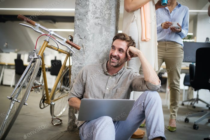 Happy coworker businessman carrying bicycle in modern office