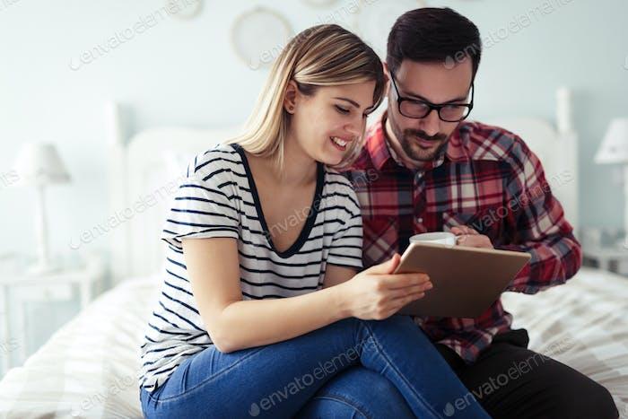 Glückliches Paar mit digitalem Tablet im Schlafzimmer