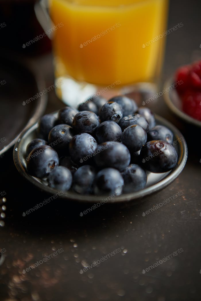 Close up on fresh blueberries placed on ceramic saucer on dark rusty table