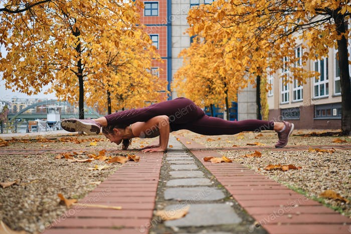 Attractive sporty girl in sportswear doing yoga exercises on empty city street
