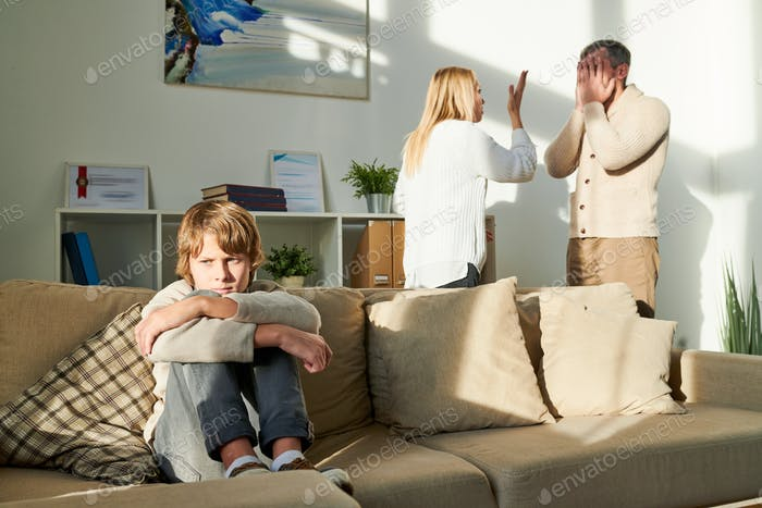 Depressed boy suffering from parents conflict