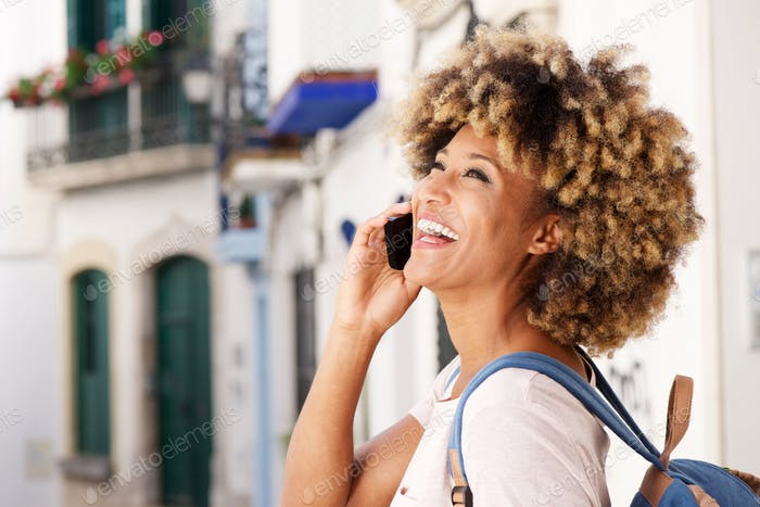 Close up cheerful young african american female talking on cellphone