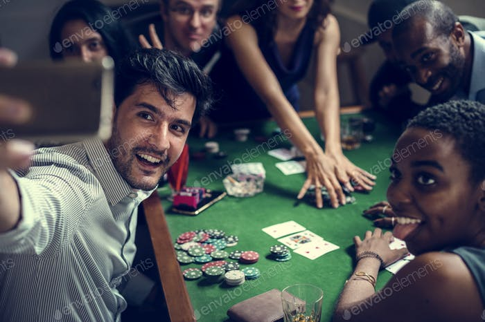 Group of people playing gamble in casino and taking selfie