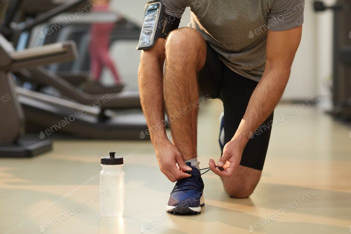 Sportive Man Tying Shoes Indoors