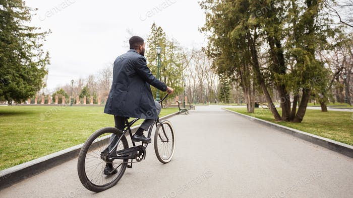 Handsome afro businessman riding his bike in park