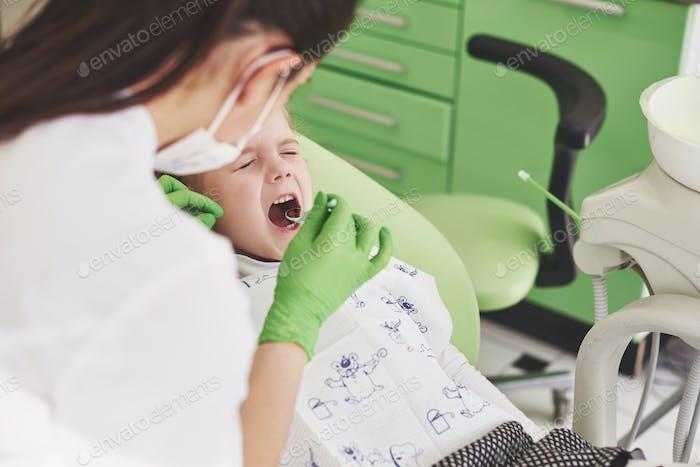 Zahnuntersuchung in der Zahnarztpraxis. Zahnarzt untersucht Mädchen Zähne in der Zahnärzte Stuhl