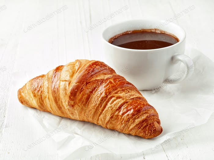 freshly baked croissant and coffee cup
