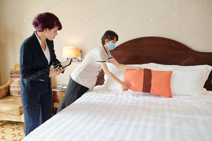 Manager looking at maid making bed