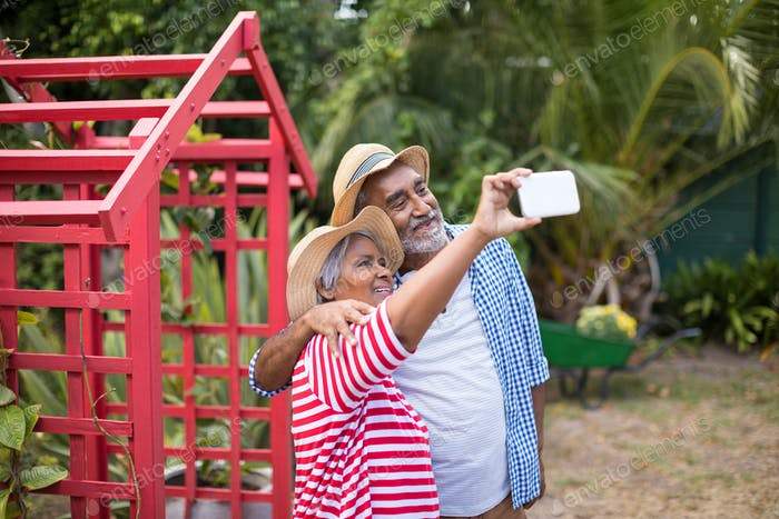 Couple taking selfie while standing in yard