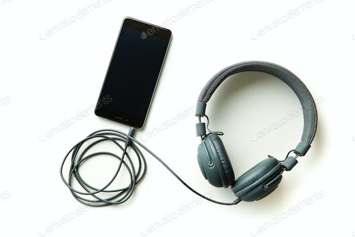 Graue Vintage-Kopfhörer und Handy.