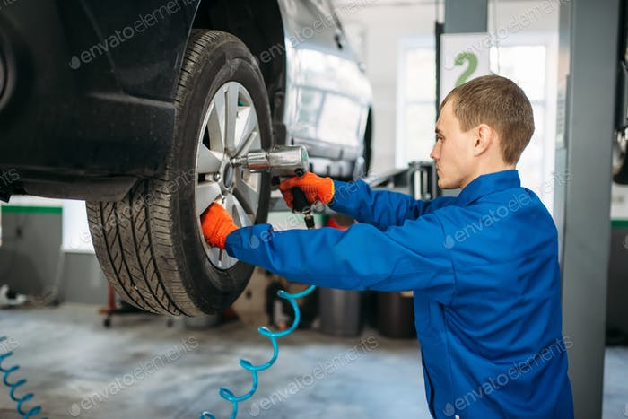 Mechanic unscrews the wheel with pneumatic wrench