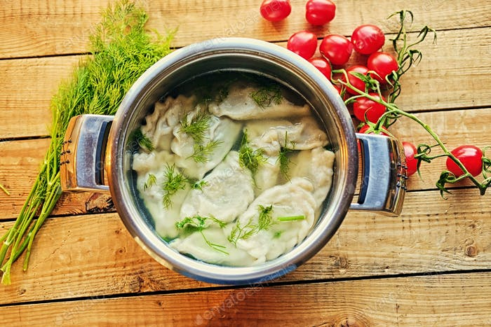 Boiled dumplings with parsley in a pot.