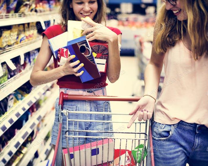 Women choosing food from a supermarket shelf