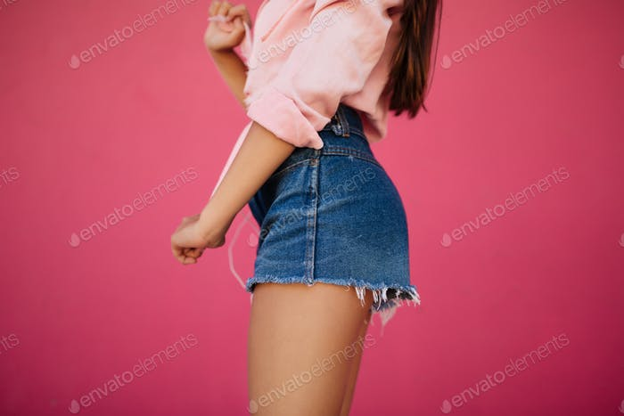 Beautiful photo of girl body in denim shorts and shirt on pink background