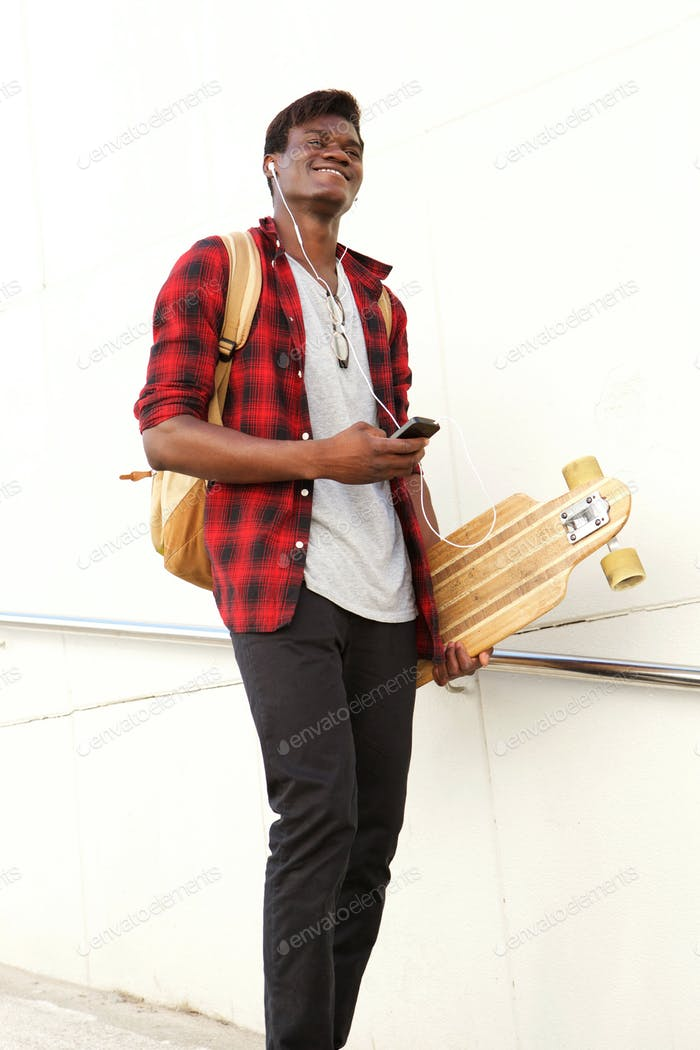 Full length cool african man with skateboard and mobile phone walking outdoors and smiling